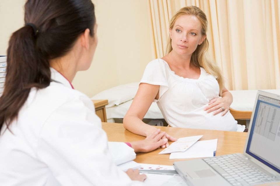 Doctor with laptop and pregnant woman in doctor's office