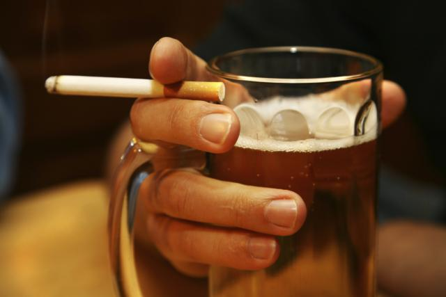 Hand holding a cigarette and beer mug
