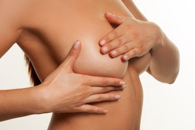 Close up of a naked woman checking foro breast cancer manipulating her breast tissue with her hands to check for lumps or abnormalities